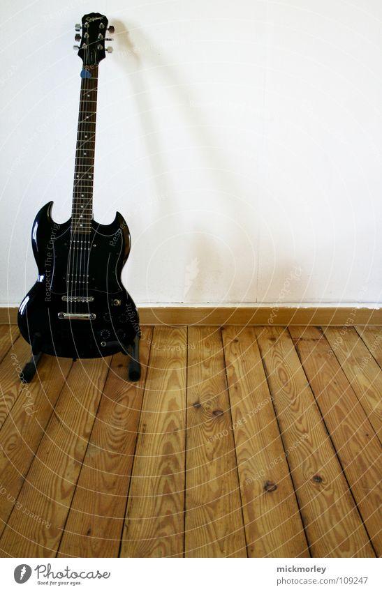 sg home sweet home Elektrogitarre elektrisch schwarz Saite Ständer Wand weiß Holz Holzfußboden Faser Holzfaser Rockband Konzert Musik Gitarre Schnur name