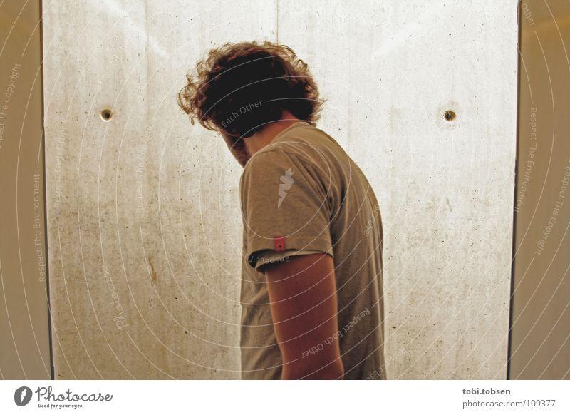 Mann im Aufzug, vor Wand mit zwei Löchern Hölle Licht Oberlicht Beton Erkenntnis gehorsam böse schwarz grau geheimnisvoll Loch T-Shirt Einbahnstraße Fahrstuhl