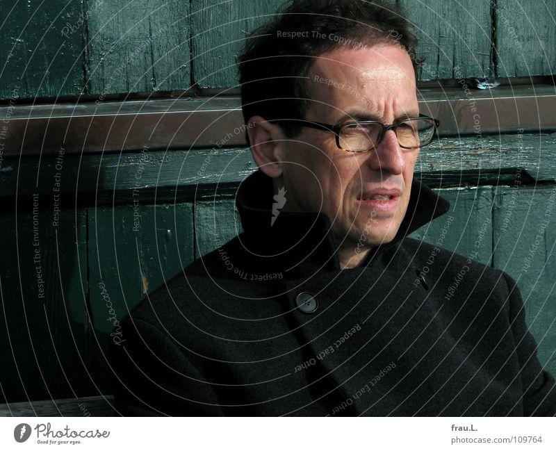 Herr A. in Farbe Mann Brille kalt Winter Herbst frieren genervt Nervosität Denken Stirnfalte Mantel Kragen Holzwand lackiert Wut Ärger junger Alter nachdenken