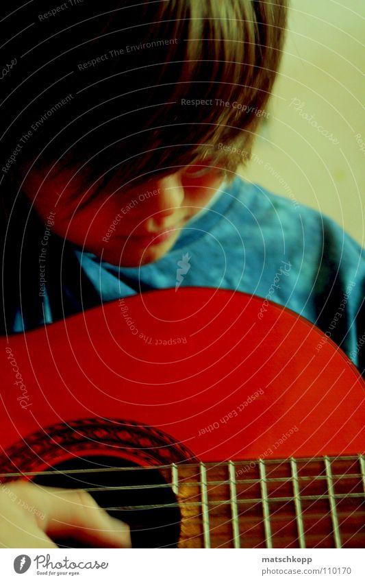 Junge.mit.Gitarre ? maskulin braun Musikinstrument Saite Hand Spielen T-Shirt Batik Holz Lippen Wand untergehen Konzentration langhaarig seltsam Boy