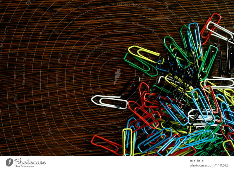 klammerchaos Büroklammern chaotisch durcheinander mehrfarbig Holz gelb weiß rot-schwarz grün beweglich Draht Zusammenhalt Büroklammerchaos Maserung