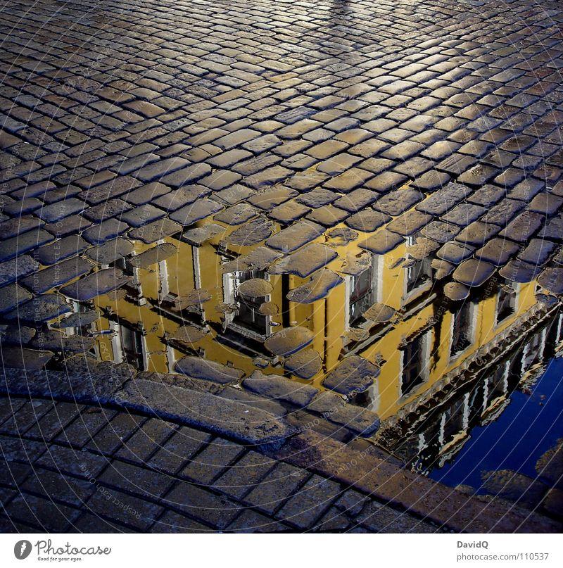 Reflexion auf der Straße Stadt blau Haus gelb grau Fassade Verkehrswege Altstadt Kopfsteinpflaster Pflastersteine Pfütze Mischung Bordsteinkante Stadthaus