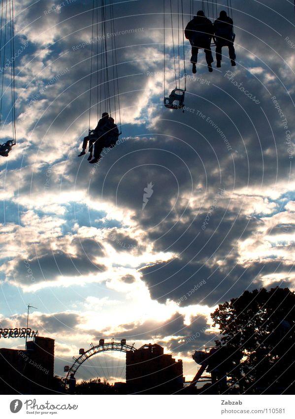 himmelskarussell Mensch Himmel blau Baum Sonne Freude Wolken schwarz Haus Spielen grau Gebäude Traurigkeit Stimmung Geschwindigkeit Seil
