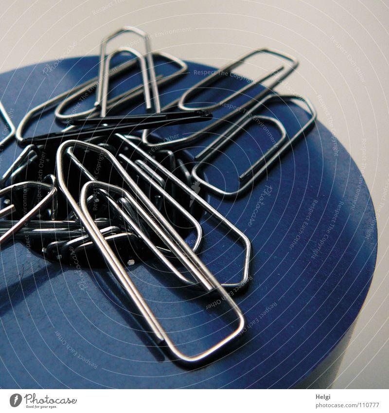 mehrere Büroklammern kleben magnetisch an einem Behälter Draht gekrümmt krumm Dose Magnet anziehen stehen Zusammensein nebeneinander klein weiß dunkel schwarz