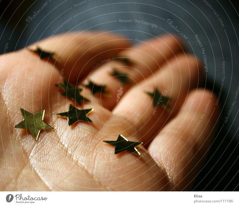Eine Person hält goldene Sterne in der Hand geben schenken Weihnachten Europa Geschenk
