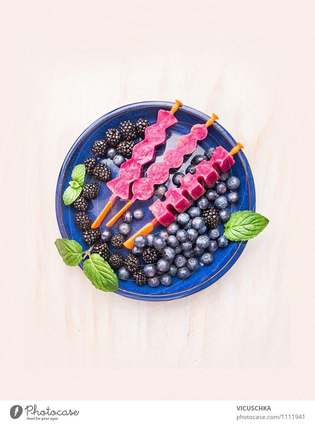 Fruchtsafteis am Stiel in blauer Teller mit Beeren Sommer Gesunde Ernährung Freude Leben Stil Garten Lebensmittel Design Tisch Speiseeis Küche Bioprodukte