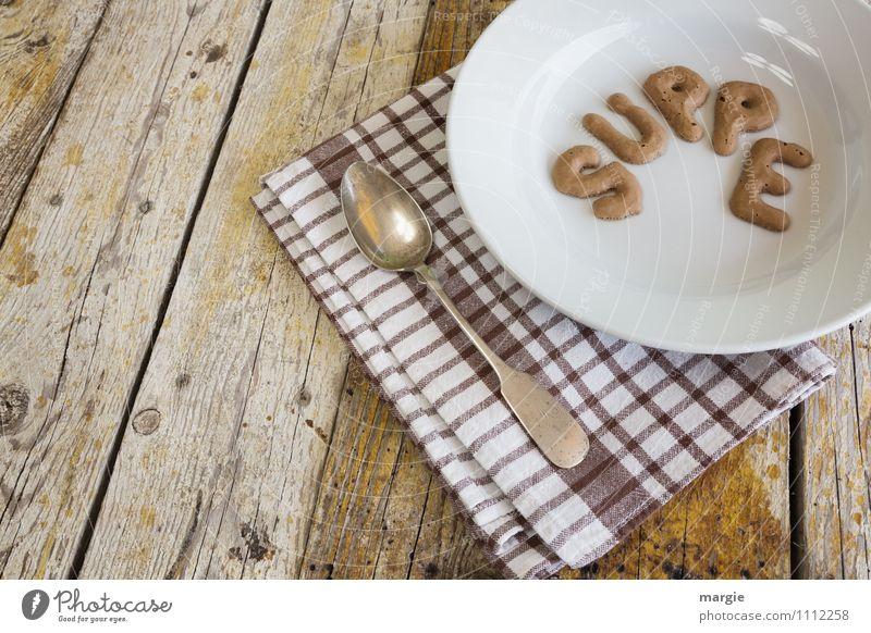 Die Buchstaben SUPPE in einem Suppenteller mit Löffel und Serviette auf einem rustikalen Holztisch Lebensmittel Eintopf Mittagessen Abendessen Büffet Brunch