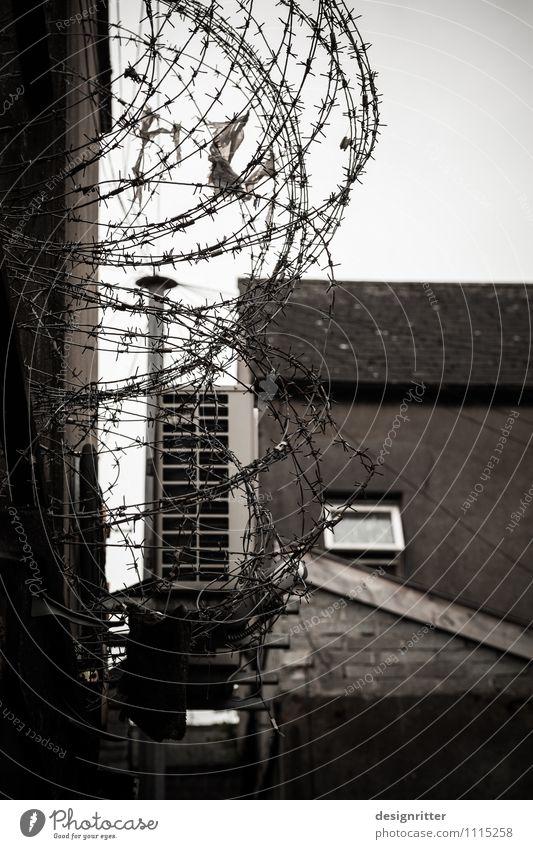 Alltäglicher Ausnahmezustand Stadt Haus Mauer Wand Fenster Dach Hof Hinterhof Zaun Stacheldraht Stacheldrahtzaun dunkel Angst Verzweiflung Rache Gewalt Hass