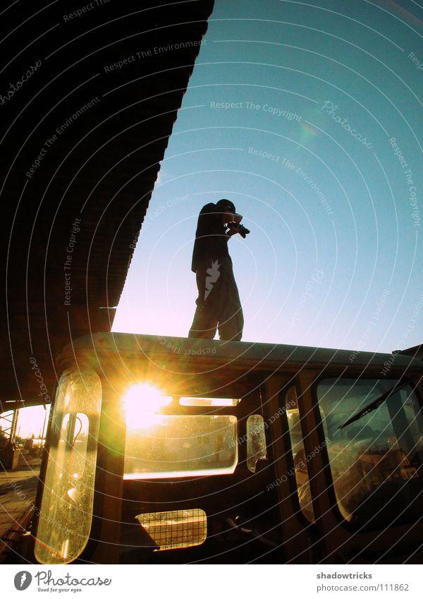 Junger Fotograf Licht Gegenlicht grün türkis Silhouette Körperhaltung Eisenbahn Industriegelände Weitwinkel Blende Mann Fotografie Fotografieren Kunst Kultur