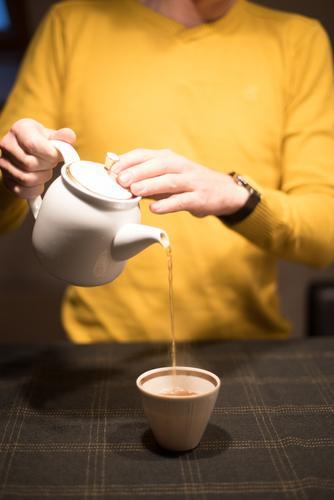 den Tee servieren Getränk Schwarzer Tee Topf Becher Teetasse Teekanne Freude Mann Erwachsene Hand Finger 1 Mensch Tisch festhalten elegant Freundlichkeit braun