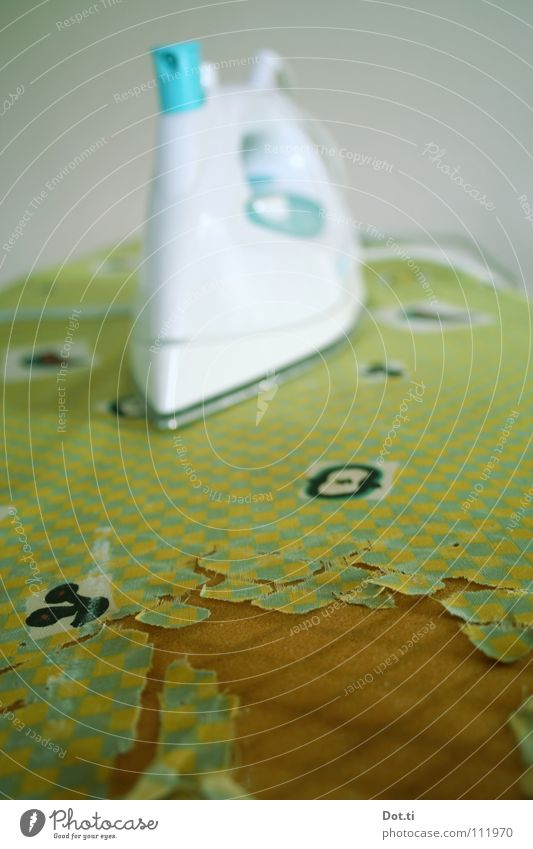 Bügelbildchen kaputt Bügeleisen Bügelbrett bügeln grün-gelb Loch Haushalt Elektrisches Gerät Bügeltuch Bügelstation schäbig zerlumpt Haushaltsunfall