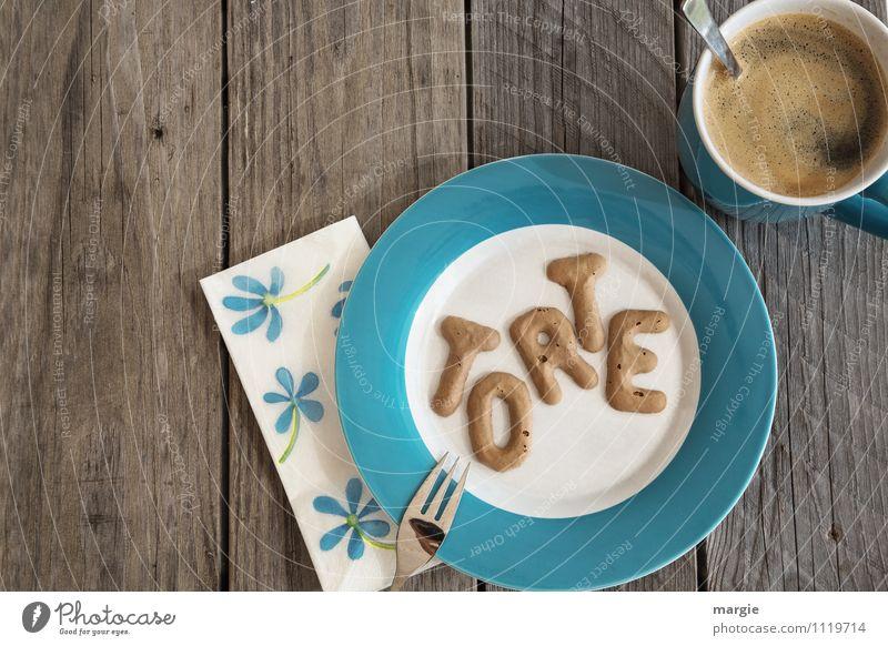 Die Buchstaben TORTE auf einem Teller mit Serviette und einer Tasse Kaffee mit Löffel auf einem rustikalen Holztisch Lebensmittel Kuchen Süßwaren Kaffeetrinken