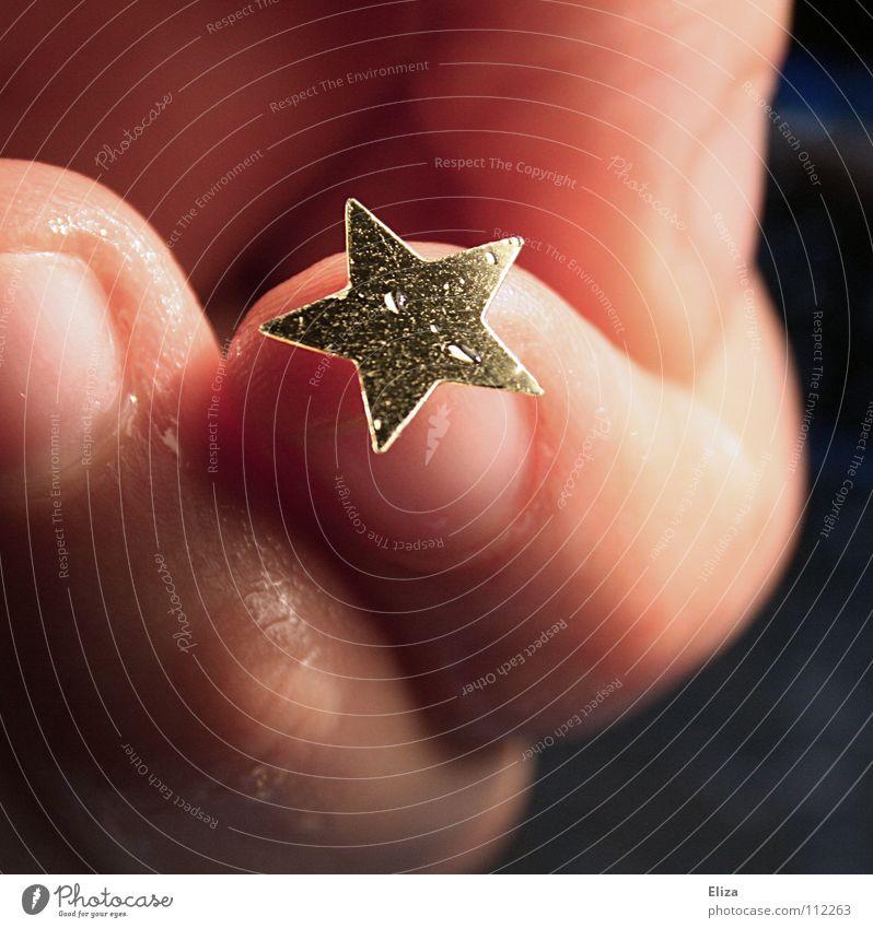 Weihnachten. Ein kleiner goldener Stern auf einem Finger Weihnachten & Advent Hand nah nass behutsam zart Himmelskörper & Weltall Stern (Symbol) zeigen Basteln