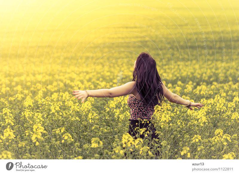 Schöne junge Frau im Sommer auf der Wiese von hinten mit ausgestreckten Armen. Das hübsche Mädchen steht in einem weiten Feld voller Raps in der Natur. Symbolisiert Glück, Gesundheit in Balance und Freiheit voller Lebensfreude gegen Burnout und Stress.