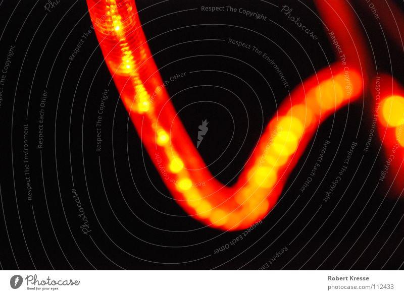 Lichterschlange rot schwarz Farbe Lampe dunkel Wärme hell orange Energiewirtschaft Elektrizität Physik gemütlich erleuchten angenehm Lichterkette
