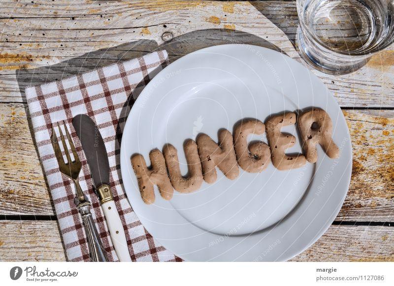 Die Buchstaben HUNGER auf einem Teller mit Messer und Gabel und Serviette und einem Glas Wasser Ernährung Diät Fasten Appetit & Hunger Getränk