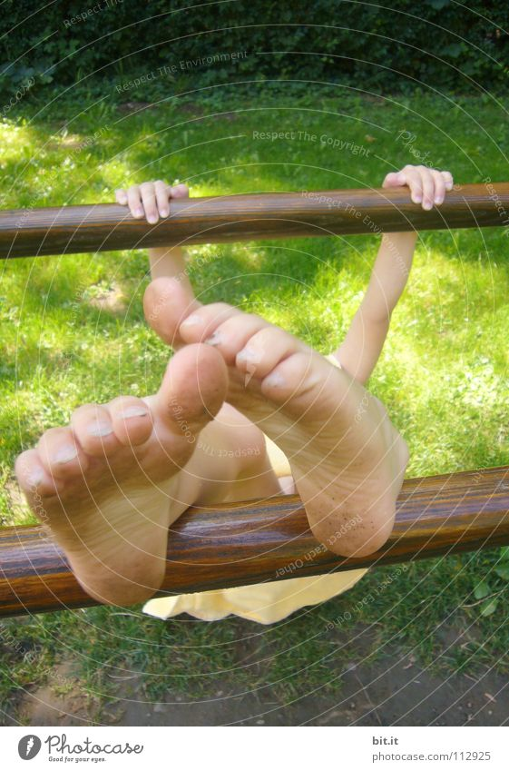 Kleines Kind hängt festgeklammert an einem Barren aus Holz, draussen in der Natur. Mädchen turnt an einer Stange, hält sich mit den Händen fest und streckt die nackten Füße nach oben. Lustige Füße, wirken durch Perspektive überdimensional groß und skurril.