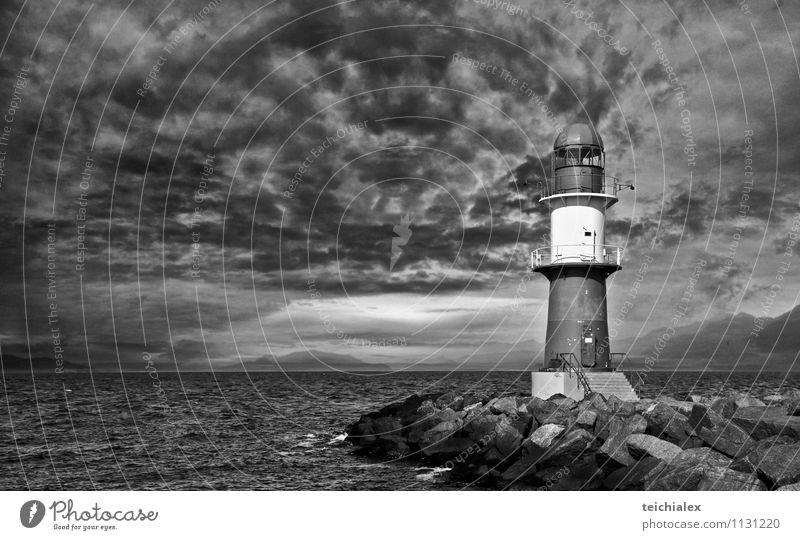 Stiller Leuchtturm Wasser Meer Wolken Strand Ferne dunkel Umwelt Stein Beton Insel Ausflug bedrohlich Abenteuer Unwetter Schifffahrt Sehenswürdigkeit