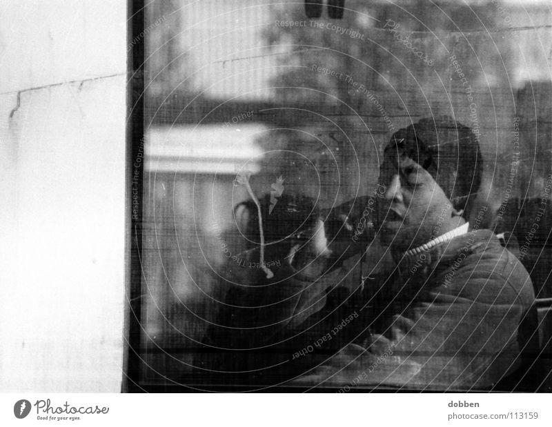 das zweite Gesicht... Mann Handy Telefon Mütze Fenster dreckig Sonnenbrille Kölner Verkehrs-Betriebe Schwarzweißfoto Kommunizieren Eisenbahn Bahnfahrer