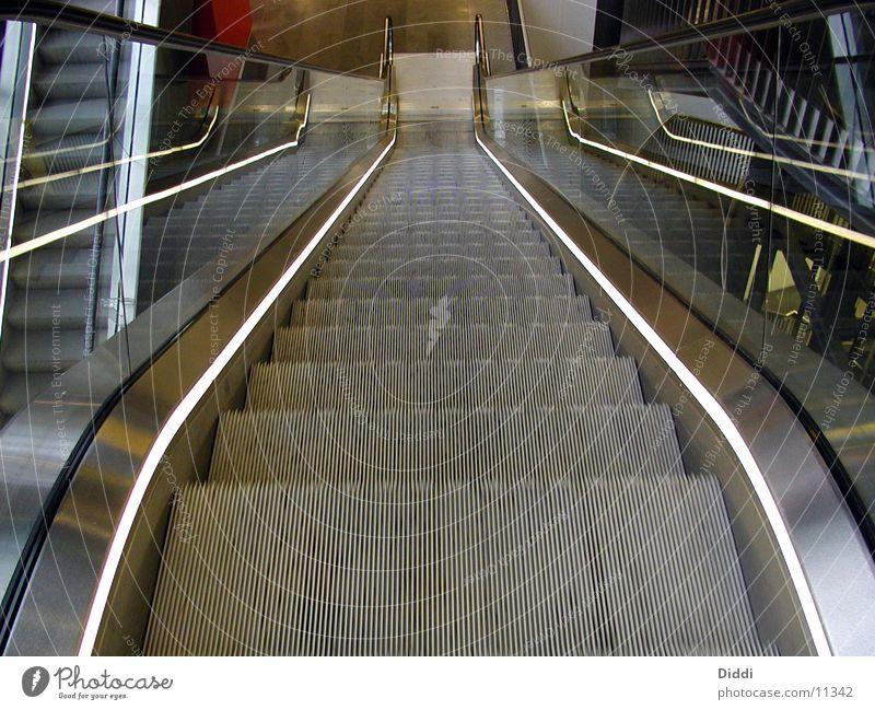 Rolltreppe oben Architektur Treppe Bewegung ab Leerfahrt leer Menschenleer Zentralperspektive Metall abwärts Treppengeländer Glas Beleuchtung