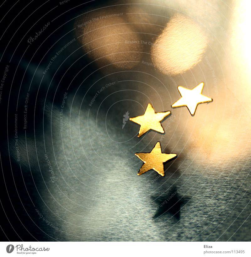 Drei goldene Sterne auf unscharfem Hintergrund mit Lichtern und schönem Bokeh; Weihnachten, Advent Weihnachtsdekoration Spielen Winter Dekoration & Verzierung