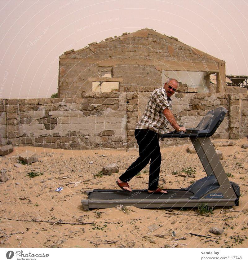 Home Trainer Mann Haus Sport Mauer Sand laufen gefährlich Fitness Laufsport trocken Wüste verfallen Sport-Training Sonnenbrille Ruine kariert