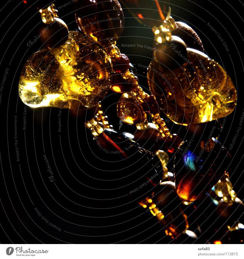 kette II Perle dunkel gelb diagonal Glasperle Gegenlicht Schmuck Kunst Kunsthandwerk Makroaufnahme Nahaufnahme Reichtum Kette