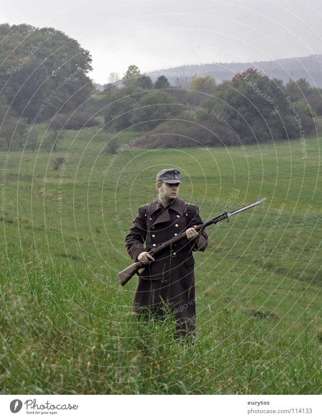 Heimatfront. Gewehr Uniform Wiese Baum Baseballmütze Mantel Bayonett Wolken grau Krieg Rucksack Wald Mann Armee Soldat kämpfen obskur Weide Natur Kappe War