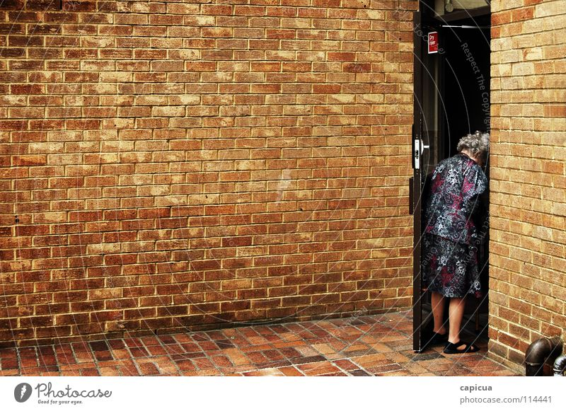 The city is a lonely place Stadt Trauer Verzweiflung Frau alone brick old woman elderly old age grandmother Bekleidung pipes sad Mauer