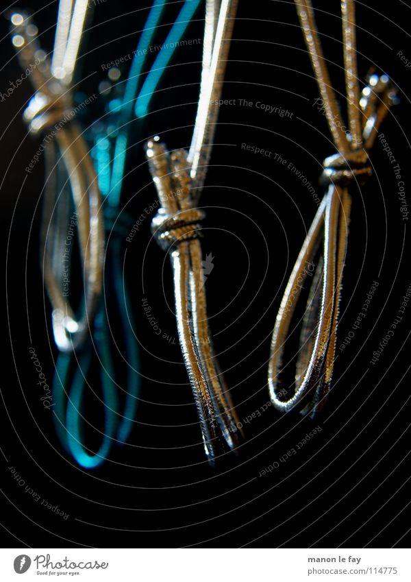 Nach dem Fest ist vor dem Fest blau schwarz Schnur hängen silber aufhängen Objektfotografie Schlaufe binden Gummiband Vor dunklem Hintergrund