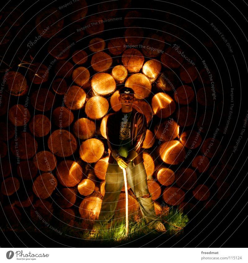 Holzfäller Schichtarbeit Taschenlampe Axt Brennholz rund Breitbeinig spreizen Licht Streifen Gras dunkel lässig unheimlich gruselig Langzeitbelichtung