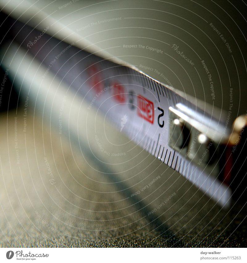 Das Maß ist voll Maßband Maßeinheit Zentimeter Norm Lücke Tisch Nahaufnahme Tiefenschärfe Unschärfe Präzision Handwerk din Genauigkeit Schatten Metall