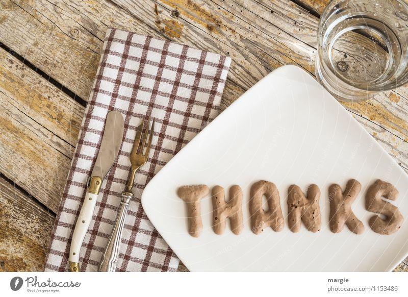 Die Buchstaben THANKS  auf einem Teller mit Serviette, Messer und Gabel und Wasserglas auf einem rustikalen Holztisch Ernährung Fastfood Fingerfood