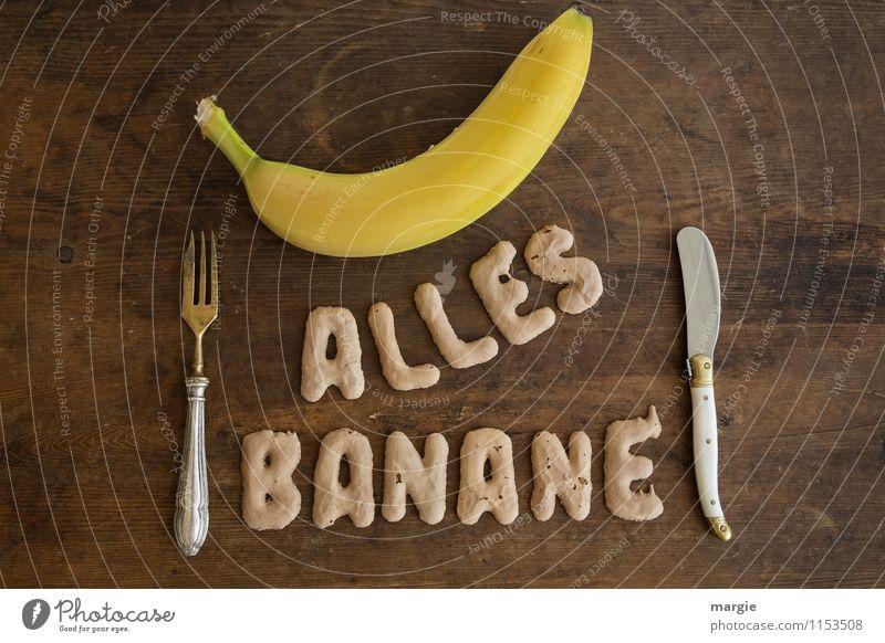 Die Buchstaben ALLES BANANE mit einer Banane und Messer und einer Gabel auf einem rustikalen Holztisch Lebensmittel Frucht Ernährung Frühstück Mittagessen