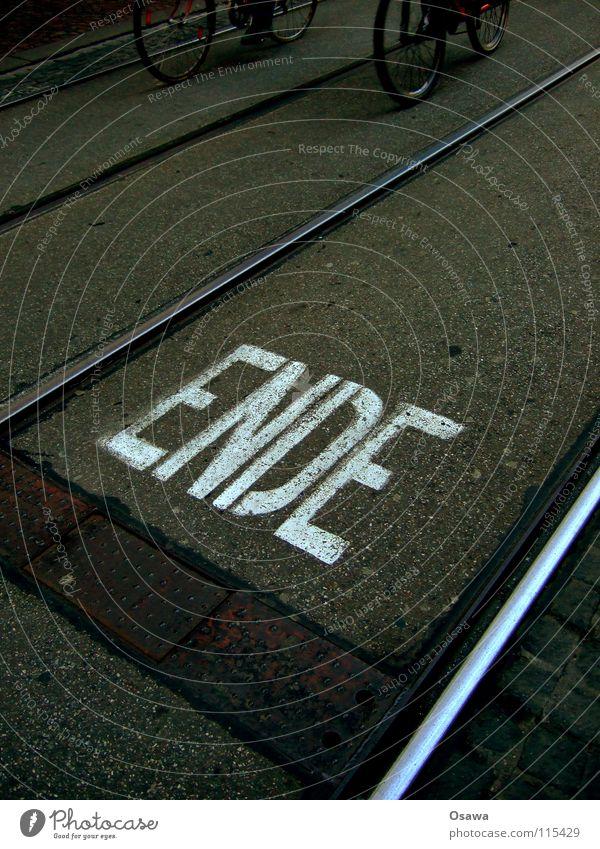 Ende Gleise Straßenbahn Stahl Asphalt Teer schwarz grau weiß Buchstaben Wort Information Mitteilung Fahrrad Fahrradweg dunkel glänzend dunkelgrau Gasse Graz