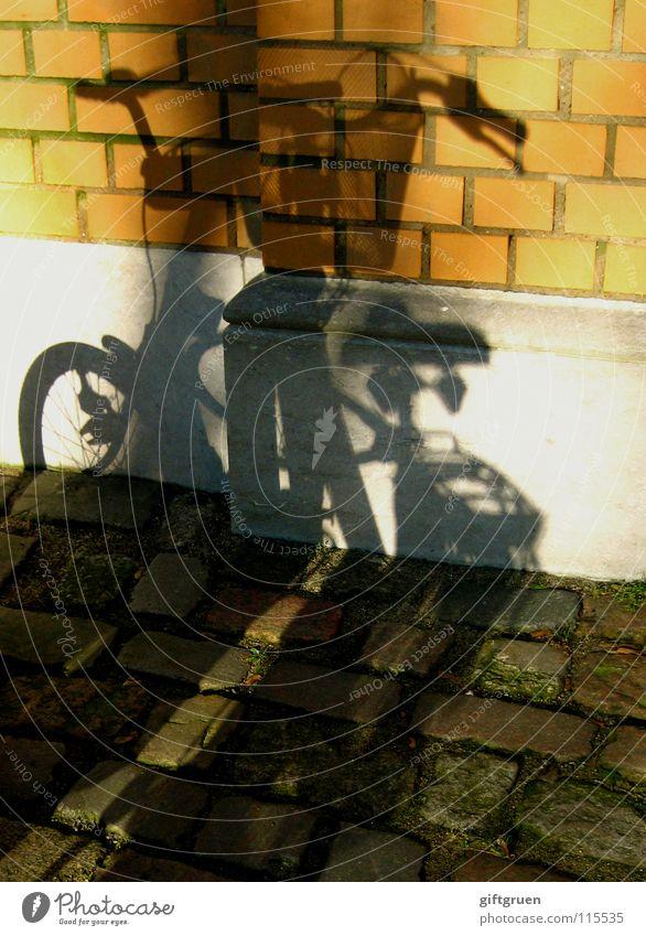 schattendasein eines drahtesels Fahrrad Schatten Licht Mauer Backstein fahren Schattendasein Sonnenbad Spielen Freizeit & Hobby Verkehr werfen Stein