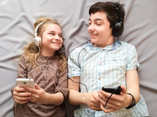 Topaufnahme von Bruder und Schwester beim gemeinsamen Musikhören über Smartphones Freude Glück Mädchen Junge Geschwister Familie & Verwandtschaft 2 Mensch