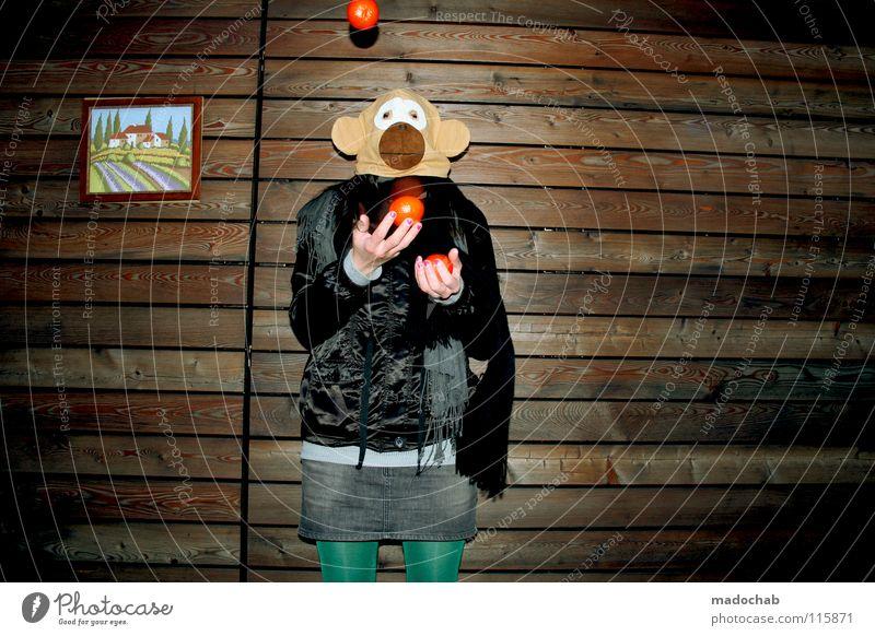 Junge Frau mit Affenmaske jongliert Mandarinen wie im Zirkus Affentheater Regenschirm Mütze kalt gefühlsarm unpersönlich Gürtel Karneval Gute Laune Bekleidung