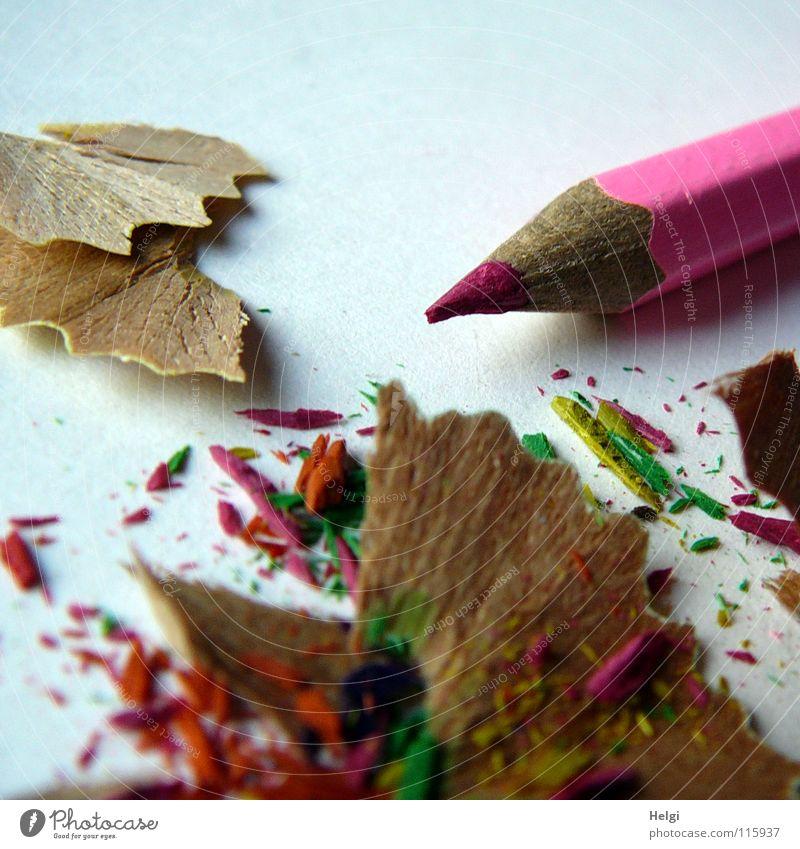 angespitzter Buntstift liegt mit dem Abfall auf dem Tisch Anspitzer Schreibstift Farbstift Holz Gesichtsausdruck mehrfarbig Müll lang dünn rosa Papier Block