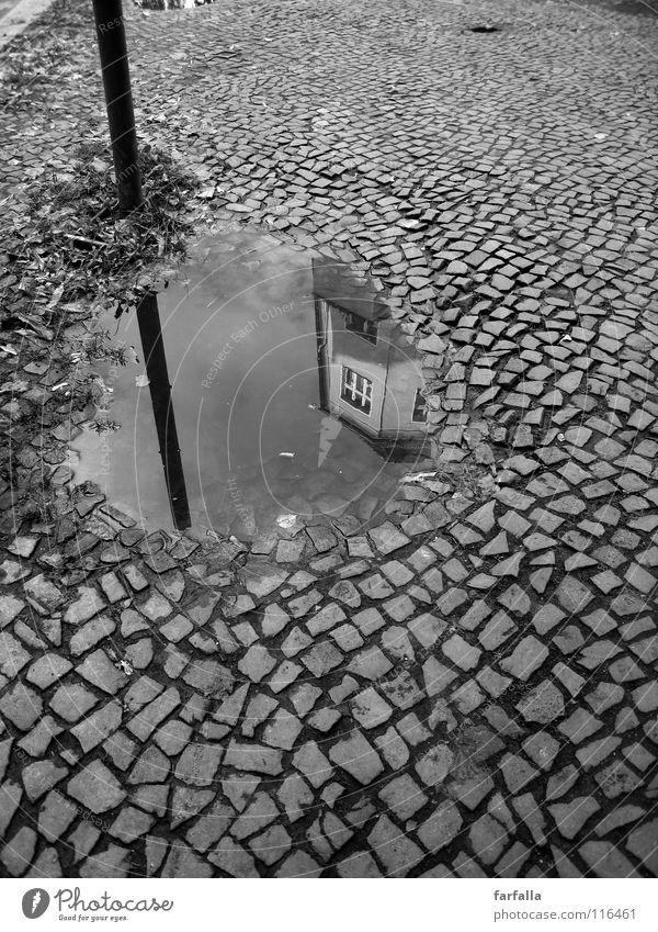 Slop Pfütze Reflexion & Spiegelung Stab Haus Stadt dunkel b/w Schwarzweißfoto Straße kopfpflaster hell