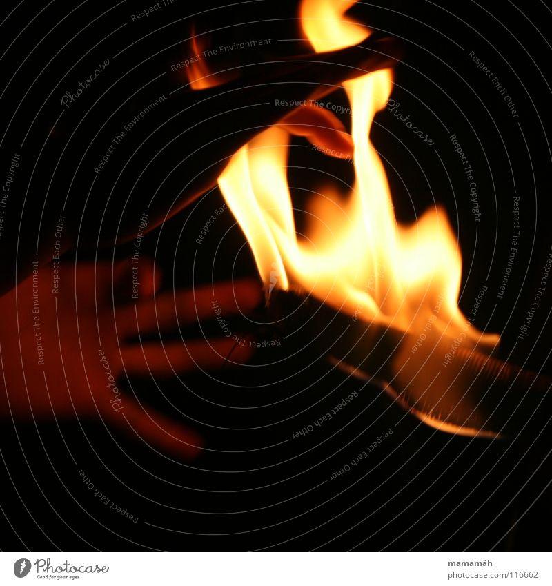 Hand ins Feuer Finger Wärme dunkel heiß hell Glut Flamme Fackel brennen geheimnisvoll Farbfoto Außenaufnahme Nacht Bewegungsunschärfe Brandgefahr
