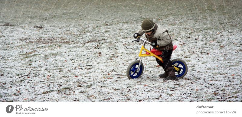 plötzlicher Wintereinbruch Kind Freude kalt Schnee Spielen Junge Wege & Pfade Eis Fahrrad stoppen Konzentration Mütze frieren Fahrradfahren Gelände