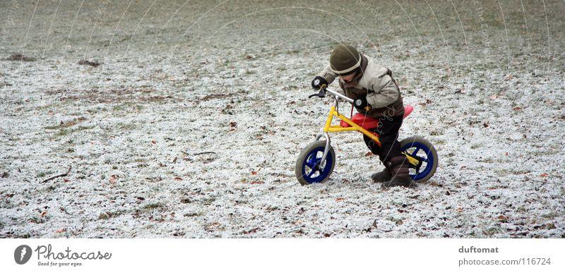 plötzlicher Wintereinbruch Kind Winter Freude kalt Schnee Spielen Junge Wege & Pfade Eis Fahrrad stoppen Konzentration Mütze frieren Fahrradfahren Gelände