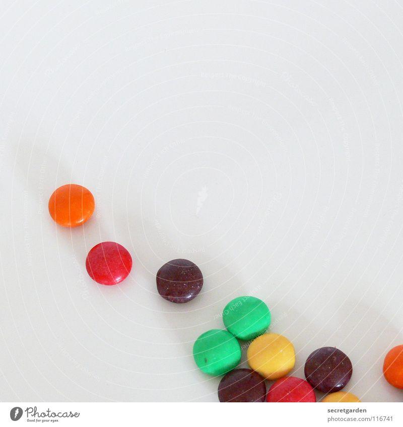 11 übriggeblieben Schokolade Schokolinsen rot gelb grün Überzug Zucker dünn Süßwaren weiß Tisch mehrfarbig Ernährung Pause klein Erinnerung