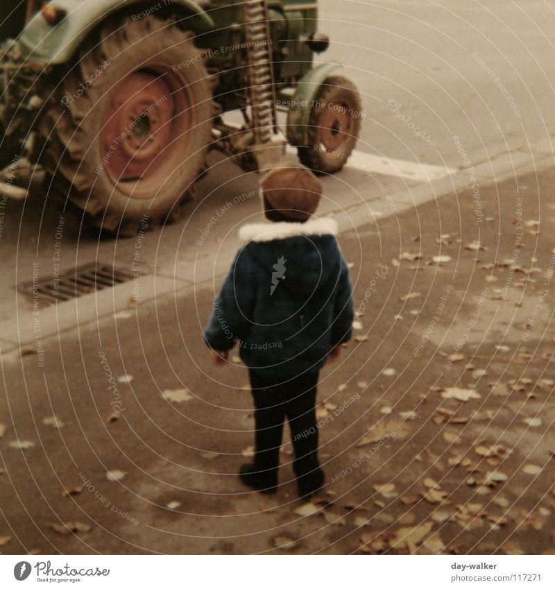 Mensch und Technik Kind Junge Traktor Siebziger Jahre Maschine Asphalt Blatt Bürgersteig retro erstaunt fahren stehen Straße Rad staunen Respekt ich laufen