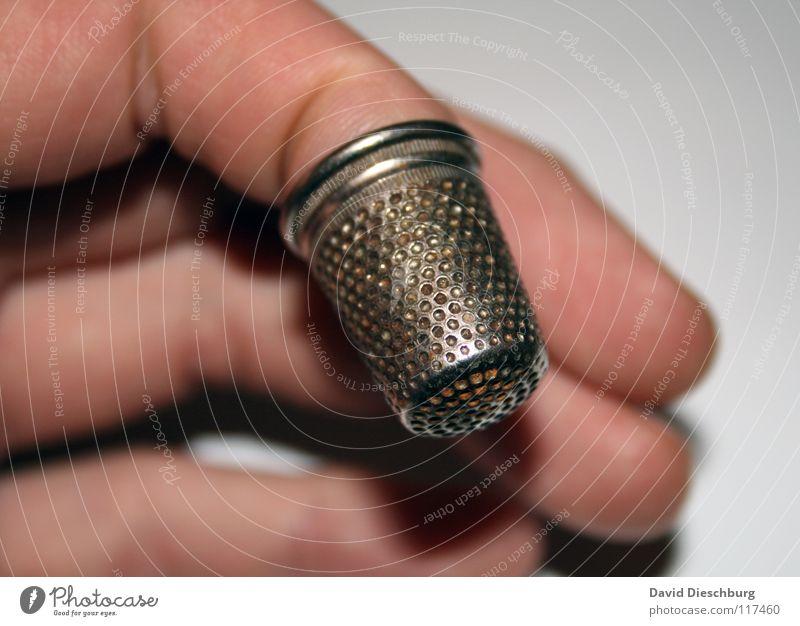 Tapferes Schneiderlein Hand Finger Nähen Unschärfe rund antik Handwerk Kunst Kultur Nadel silber tapfer Kreis Nahaufnahme Nähgarn Fingerschutz gelocht