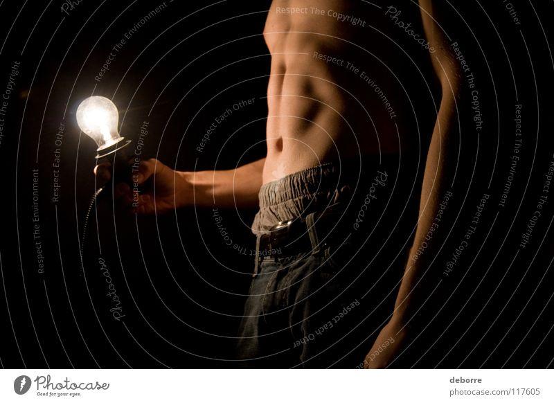 Junger Mann posiert oben ohne mit Glühbirne im Dunkeln. Nahaufnahme Kerl Licht nackt schwarz Arme schlecht Magen Beine Bauch Kumpel Typ Haut Jeanshose Knolle