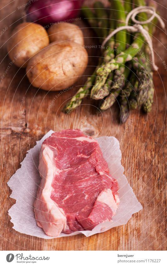 Viktualien Lebensmittel Fleisch Gemüse Ernährung Bioprodukte Billig gut roh Steak Rindersteak Spargel Kartoffeln Zwiebel rustikal Holzbrett Papier Fett