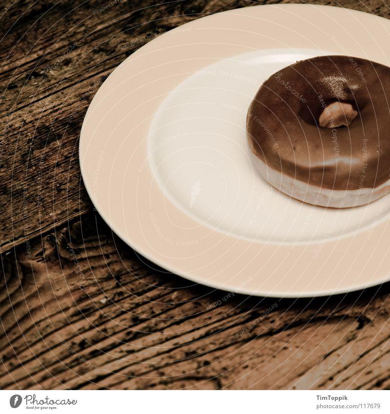 Donutella Tisch Holztisch Maserung Holzstruktur Küche Teller Tellerrand rund Krapfen Fett ungesund Kreis kreisrund Hefe Backwaren Teilchen Ernährung Bäckerei