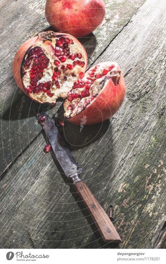 Granatapfel auf Vintage Holztisch Frucht Dessert Essen Vegetarische Ernährung Diät Saft Tisch alt dunkel frisch retro saftig rot Farbe hölzern Messer